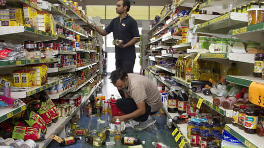 Consumer staples Staff members clear stock from their shop floor in the small Wairarapa town of Eketahuna on January 20, 2014 after a strong 6.3-magnitude earthquake rattled New Zealand