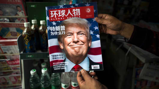 A copy of the local Chinese magazine Global People with a cover story that translates to 'Why did Trump win' is seen with a front cover portrait of US president-elect Donald Trump at a news stand in Shanghai on November 14, 2016.