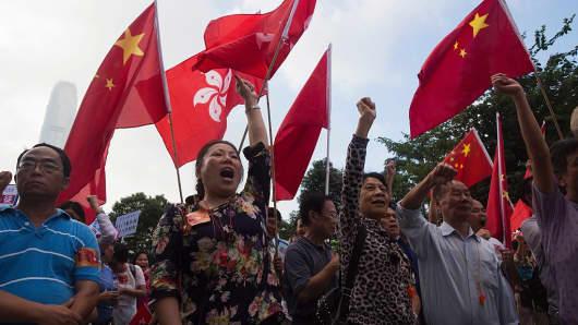 Pro-Beijing demonstrators shout slogans and wave flags outside the Hong Kong Legislative Council on November 13, 2016.