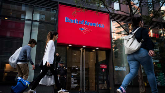 Pedestrians pass in front of a Bank of America Corp. branch in New York.
