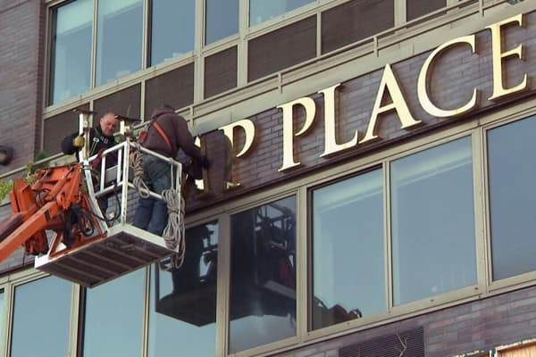Workers remove Trump's name from residential building after residents petitioned to have his name removed.