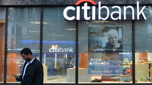 A man checks his phone near a Citibank branch on October 5, 2016 in Washington, DC.