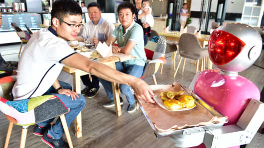 A 'female' robot waiter delivers meals for customers at robot-themed restaurant on May 18, 2015 in Yiwu, Zhejiang province of China.