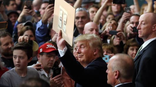 Donald Trump prepares to autograph a cardboard with two dollars taped to it as he greets people during a campaign event at Hampshire Hills Athletic Club on February 2, 2016.