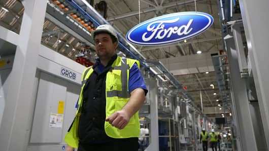 An employee walks past a Ford logo in a Ford factory.