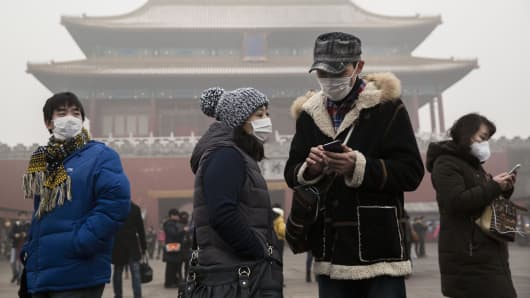 Chinese tourists wear masks as protection from the pollution outside the Forbidden City during a day of high pollution in Beijing, China.