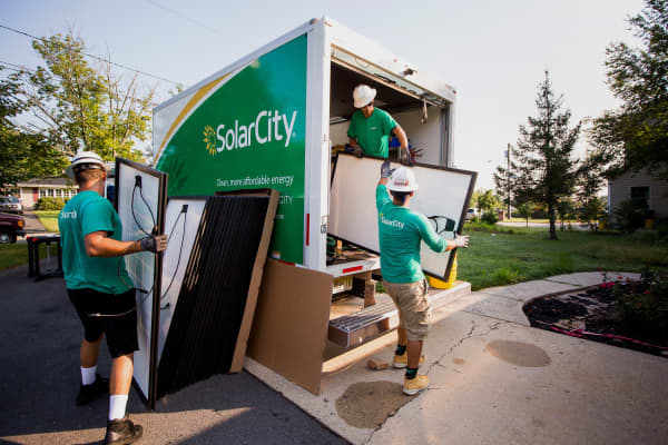 SolarCity Corp. employees unload solar panels from a truck