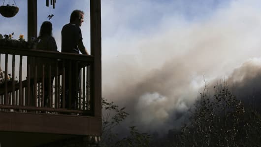 Eric and Vebbra Willey watch from their porch as the Rock Mountain wildfire approaches closer to their home on Wednesday, Nov. 16, 2016, in Tate City, Ga. Residents are under a pre-evacuation order as firefighters work to keep the fire away from homes.