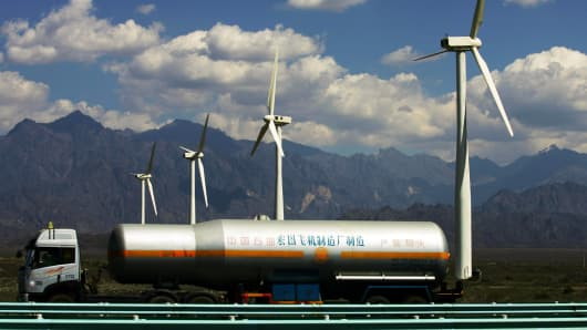 A oil truck runs past wind turbines at the Dafancheng Wind Power Plant.