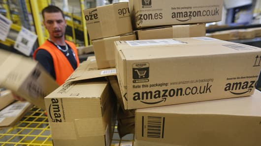 A worker prepares packages for delivery at a Amazon warehouse.