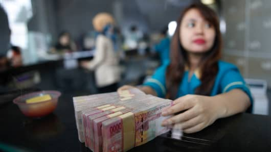 A teller at a money changer handles Indonesia rupiah bank notes in Jakarta, Indonesia November 11, 2016.