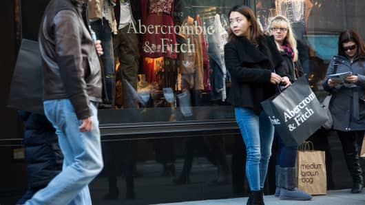Pedestrians stand outside of the Abercrombie & Fitch Co. store on 5th Avenue in New York, U.S., on Sunday, Feb. 28, 2016.