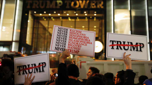 Demonstrators hold signs outside Trump Tower during a protest march against President-elect Donald Trump in Manhattan, New York, U.S. November 9, 2016.