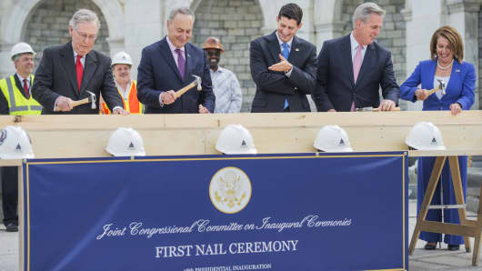 Speaker Paul Ryan, R-Wis., center, reacts to the technique of Sen. Charles Schumer, D-N.Y., as Senate Majority Leader Mitch McConnell, R-Ky., far left, House Majority Leader Kevin McCarthy, R-Calif., and House Minority Leader Nancy Pelosi, D-Calif., participate in a First Nail Ceremony that launches the construction of the Inaugural p