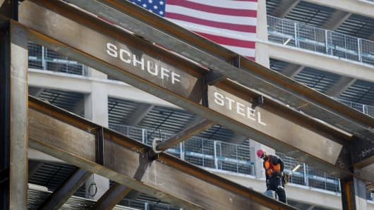 An American flag is seen as contractor walks on a steel beam while working on the Korean Air Lines Co. Wilshire Grand hotel and office building in downtown Los Angeles, California