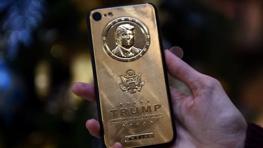 An employee of Caviar Phones, a Russian-Italian company specializing in smartphone customization, displays a special gold-plated iPhone 7 smartphone bearing the likeness of US President-elect Donald Trump - at a minimum price of 197 000 rubles (2755 euros / 2971 dollars) - in the company's boutique outside Moscow on November 14, 2016.