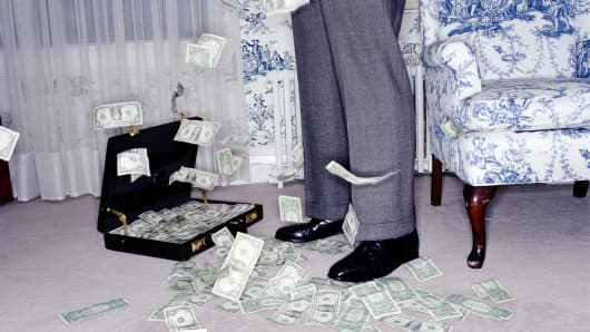 US banknotes falling around man in hotel room, low section