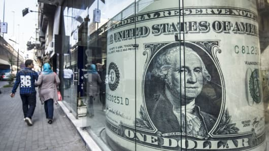 People walk past a currency exchange shop displaying a giant US dollar in downtown Cairo, Egypt on November 3, 2016.