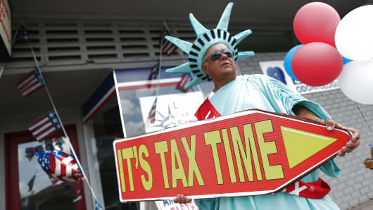 A man directs people to the Liberty Tax Service office as the deadline to file taxes looms on April 15, 2016 in Miami, Florida.