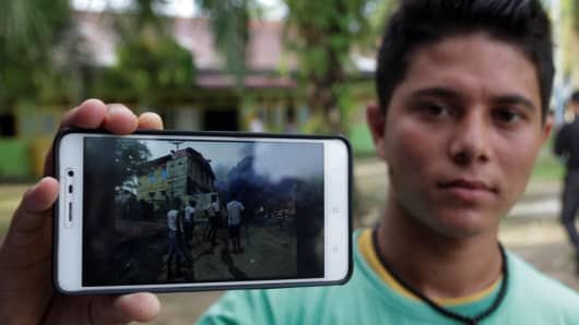 November 21, 2016: A Rohingya man in Indonesia shows photos of the violence experienced by Rohingyas in Myanmar.