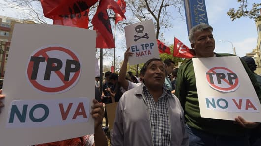 Protesters hold placards against the Trans Pacific Partnership during a rally on the sidelines of the Asia Pacific Economic Cooperation Summit in Lima