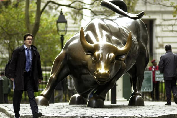 A man walks past the charging bull statue near the New York Stock Exchange.