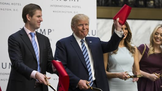 Donald Trump (C) cuts the ribbon with his son, Eric Trump (L), and wife, Melania Trump (R), during opening ceremony for the Trump International Hotel, Old Post Office, in Washington, USA on October 26, 2016.