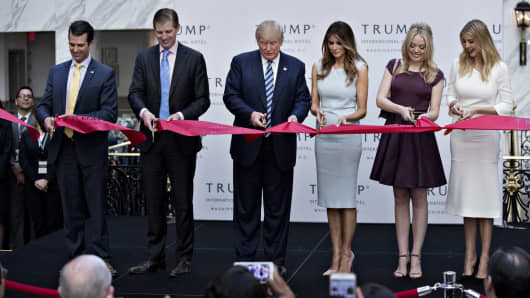 Donald Trump, center, cuts a ribbon with his sons Donald Trump Jr., from left, Eric Trump, his wife Melania Trump and his daughters Tiffany Trump and Ivanka Trump during the grand opening ceremony of the Trump International Hotel in Washington, D.C., Oct. 26, 2016.