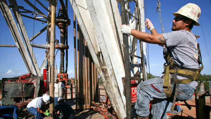 Workers operate a drilling rig for an EBR Energy LP natural gas well near Columbus, Texas.