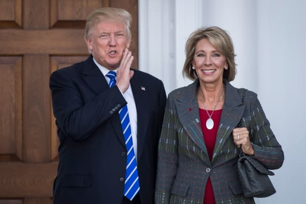 President-elect Donald Trump stands with Betsy DeVos after a meeting at Trump National Golf Club Bedminster in Bedminster Township, N.J. on Saturday, Nov. 19, 2016.