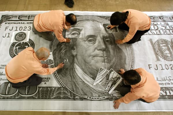 Crafworkers with loopes compare blown-up sections of counterfeit hundred-dollar bills with a sample legitimate bill expanded 400 times larger than the real size