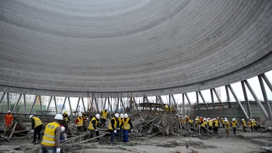 Workers search through the remains of a collapsed platform in a cooling tower at a power station at Fengcheng, in China's Jiangxi province on November 24, 2016. At least 40 people were killed when part of a power station under construction in China collapsed on November 24, the official Xinhua news agency reported, the latest industrial accident in a country with a dismal safety record.