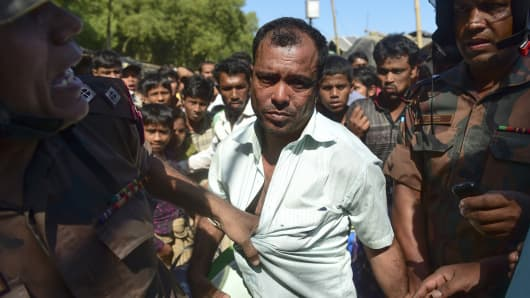 Border Guard Bangladesh personel detain a suspected Myanmar citizen (C), who is suspected by Rohingya escapees of spying for Myanmar, at a refugee camp in Teknaf in southern Cox's Bazar district on November 24, 2016. Dhaka has called on Myanmar to take 'urgent measures' to protect its Rohingya minority after thousands crossed into Bangladesh in just a few days, some saying the military was burning villages and raping young girls.