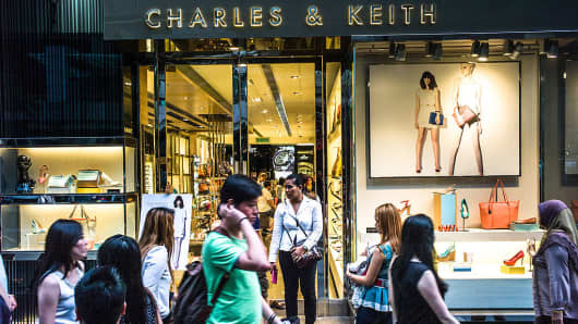 Pedestrians walk past a Charles & Keith store in downtown Kuala Lumpur, Malaysia.