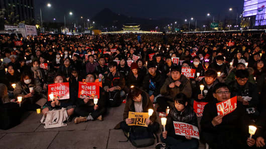 People hold candlelight with shout slogans during an anti-government rally at Gwanghwamoon square in Seoul, South Korea.
