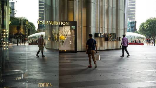 A shopper walks past a Louis Vuitton store in the Ion Orchard mall on Orchard Road in Singapore.