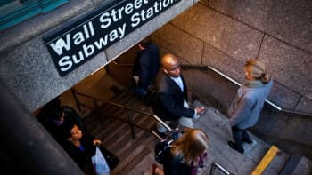 Commuters walk through a Wall Street subway station near the New York Stock Exchange.