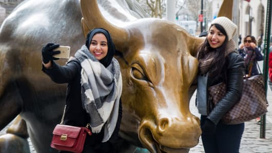 Tourists pose for pictures with the famous bull sculpture near Wall Street in New York.