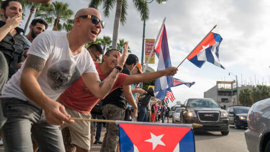 People take to the streets to react to the news of the death of former Cuban President Fidel Castro outside the restaurant Versailles November 26, 2016 in Miami, Florida.
