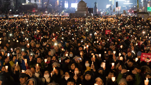 Protesters hold candles during a rally in Seoul, South Korea, on Saturday, Nov. 26, 2016.