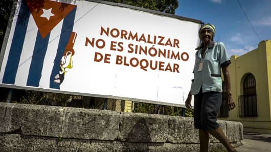 A man passes in front of a poster against the U.S. blockade to Cuba, in Havana on October 26, 2016 after the UN General Assembly adopted a resolution calling for an end to the U.S. embargo.
