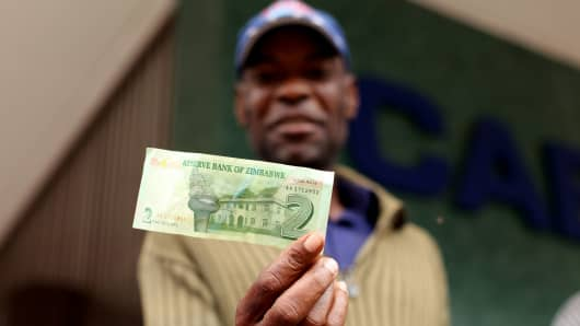 A man holds a two dollar Zimbabwean 'bond note' withdrawn in Harare, Zimbabwe on November 28, 2016.