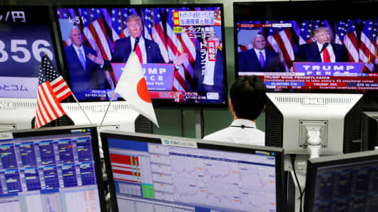 An employee of a trading company looks at monitors showing U.S. President-elect Donald Trump speaking on TV in Tokyo, Nov. 9, 2016.