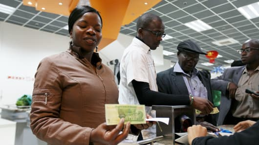 A woman holds a two dollar 'bond note' in a shop in Harare, Zimbabwe on November 28, 2016.