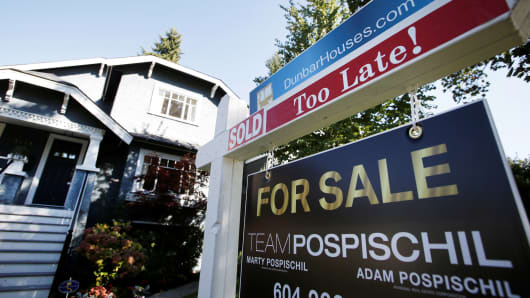 A real estate for sale sign is pictured in front of a home.