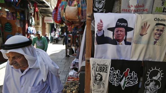 A Palestinian walks past a souvenir shop displaying T-shirts bearing images of US President Barack Obama (R) wearing a kaffiyeh and president-elect Donald Trump (L) dressed as a Hasidic Jew for sale in a souvenir shop in Jerusalem's Old City November 10, 2016.