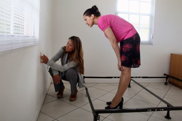 A right property agent, left, reveals a rental on the market to a prospective buyer in Miami, Florida.