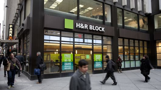 Pedestrians walk past the H&R Block Inc. flagship office in New York, U.S.