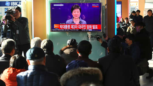 People watching a televised speech of South Korean President Park Geun-Hye at a railway station in Seoul on November 29, 2016.