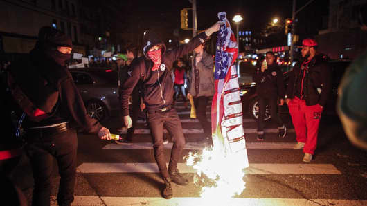 A demonstrator burns an American flag during a protest November 25, 2015 in New York City, one day after a grand jury decision not to prosecute a white police officer for the killing of an unarmed black teen in Ferguson, Missouri.